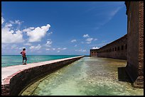 Park visitor looking, Fort Jefferson moat and seawall. Dry Tortugas National Park, Florida, USA. (color)