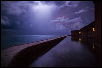 Fort Jefferson seawall at night with sky lit by thunderstorm. Dry Tortugas National Park, Florida, USA. (color)