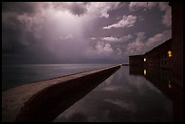 Fort Jefferson seawall at night with sky lit by tropical storm. Dry Tortugas National Park, Florida, USA. (color)