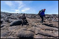 Hiker descending from Mauna Loa summit next to sign. Hawaii Volcanoes National Park, Hawaii, USA. (color)