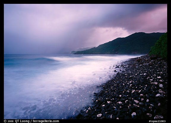 Coastline with dark rocks, light water and storm sky at sunrise, Vatia bay, Tutuila Island. National Park of American Samoa