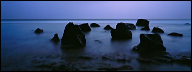 Seascape with boulders in water at dusk. National Park of American Samoa (Panoramic color)
