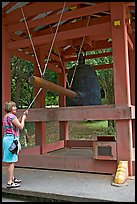 Tourist rings the sacred bell before entering Byodo-In temple. Oahu island, Hawaii, USA