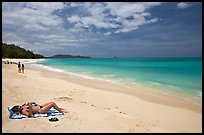 Woman sunning herself on Waimanalo Beach. Oahu island, Hawaii, USA