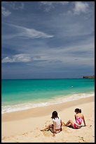Young women sitting on Waimanalo Beach. Oahu island, Hawaii, USA