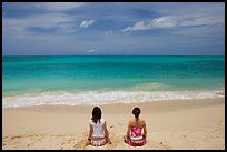Young women facing ocean in meditative pose on Waimanalo Beach. Oahu island, Hawaii, USA