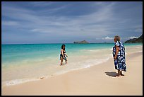 Two women, the older in hawaiian dress, on Waimanalo Beach. Oahu island, Hawaii, USA