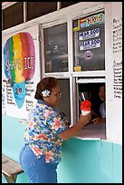 Woman with a flower in hair getting shave ice, Waimanalo. Oahu island, Hawaii, USA