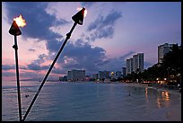 Bare flame torches and skyline at sunset. Waikiki, Honolulu, Oahu island, Hawaii, USA ( color)