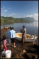 Fisherman and family pulling out net out of small baot, Kaneohe Bay, morning. Oahu island, Hawaii, USA (color)