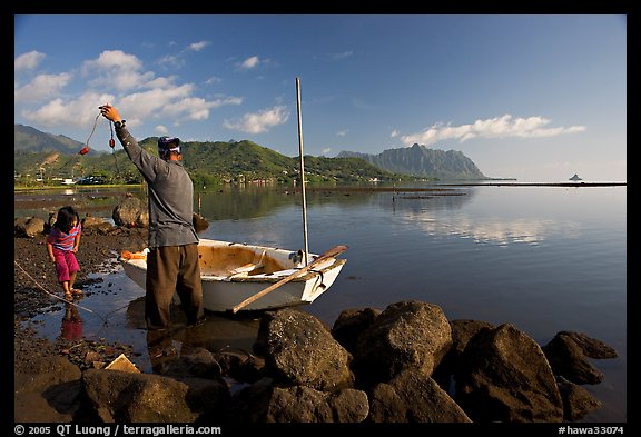 Fisherman pulling out fish out a net, with girl looking, Kaneohe Bay, morning. Oahu island, Hawaii, USA (color)