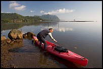 Man loading sea kayak for a fishing trip, Kaneohe Bay, morning. Oahu island, Hawaii, USA (color)