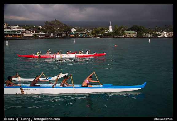 Outrigger canoes and town under storm sky, Kailua-Kona. Hawaii, USA (color)