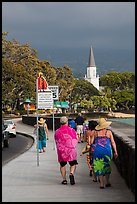 Beachgoers walking past ironman triathlon sign, Kailua-Kona. Hawaii, USA ( color)