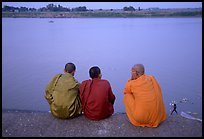 Buddhist monks sit on  banks of Tongle Sap river at dusk,  Phnom Phen. Cambodia ( color)