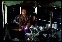 Engine and pilot at the rear of a slow passenger boat. Mekong river, Laos ( color)
