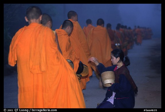 Woman gives alm during morning procession of buddhist monks. Luang Prabang, Laos (color)