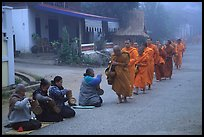 Women line up to offer alm to buddhist monks. Luang Prabang, Laos (color)