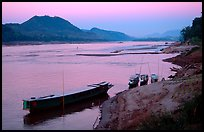 Dusk on the Mekong river framed by coconut trees. Luang Prabang, Laos