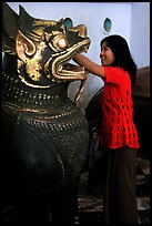 Rubbing an Angkor bronze statue at Mahamuni Paya. Mandalay, Myanmar (color)