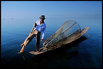 Intha fisherman on duggout with net. Inle Lake, Myanmar