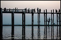 U Bein Bridge with monks and visitors strolling at dusk. Amarapura, Myanmar ( color)