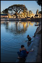 Women washing and doing laundry in lake with pagoda in background. Pindaya, Myanmar ( color)