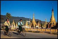 Schoolgirls riding bicycles past golden stupas. Pindaya, Myanmar ( color)