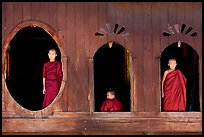 Buddhist monks looking through windows of Shweyanpyay Monastery, Nyaung Shwe. Inle Lake, Myanmar ( color)