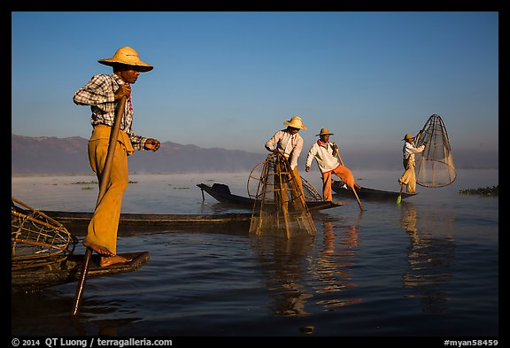 Intha fishermen standing on stern of their boats to fish. Inle Lake, Myanmar (color)