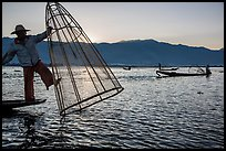 Intha fisherman standing on boat stern to lift net basket. Inle Lake, Myanmar ( color)
