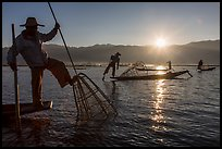 Intha fisherman using spear sticking through the top of basket to expose fish. Inle Lake, Myanmar ( color)