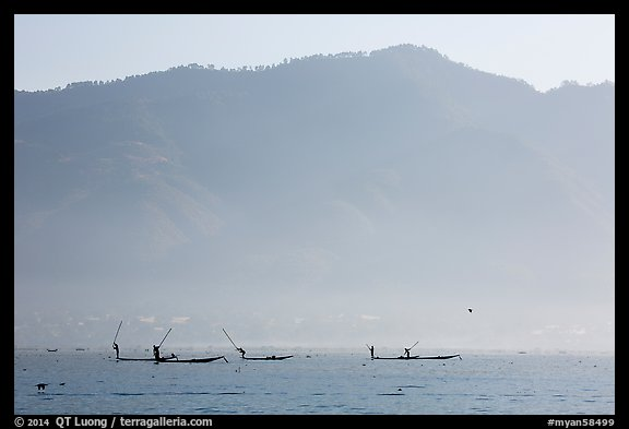 Intha fishermen in the distance using spears to stir fish, below tall hills. Inle Lake, Myanmar (color)