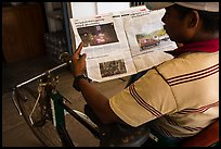 Cyclo driver looking at picture of QT Luong tour group in newspaper. Bago, Myanmar ( color)