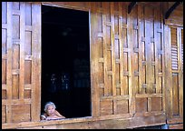 Woman looks out of teak house window. Damnoen Saduak, Thailand ( color)