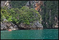 Couple paddling below steep cliffs. Krabi Province, Thailand (color)