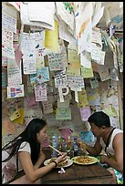 Couple eating Pad Thai below notes of praise left by customers, Ko Phi Phi. Krabi Province, Thailand ( color)