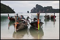 Man stepping on boats, Ao Lo Dalam, Ko Phi-Phi Don. Krabi Province, Thailand ( color)