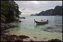 Boat, clear water, stormy skies, Phi-Phi island. Krabi Province, Thailand