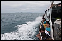 Passengers sitting on side of boat. Krabi Province, Thailand ( color)