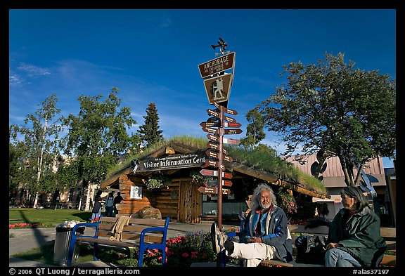 Native people sitting in front of visitor center. Anchorage, Alaska, USA (color)