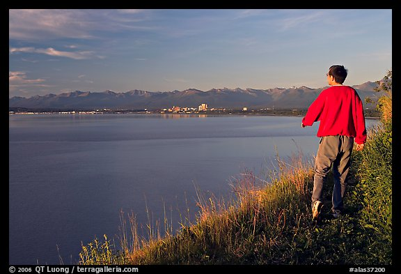 Man walking on the edge of Knik Arm in Earthquake Park, sunset. Anchorage, Alaska, USA