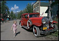 Girl on main street with red classic car. McCarthy, Alaska, USA ( color)