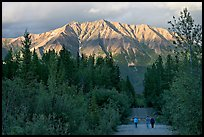 People walking on unpaved road, with last light on mountains. McCarthy, Alaska, USA ( color)