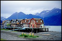 Stilt houses on the Spit, Kenai Mountains in the backgound. Homer, Alaska, USA