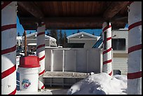 Bus stop with red candy-like stripped columns. North Pole, Alaska, USA ( color)