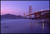 Golden Gage bridge at dusk, reflected in wet sand at East Baker Beach. San Francisco, California, USA