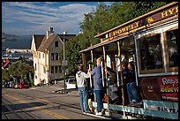Cable car plunging with people clinging on Hyde Street, late afternoon. San Francisco, California, USA ( color)
