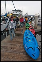 Sea kayaks and passengers awaiting loading on tour boat. California, USA (color)