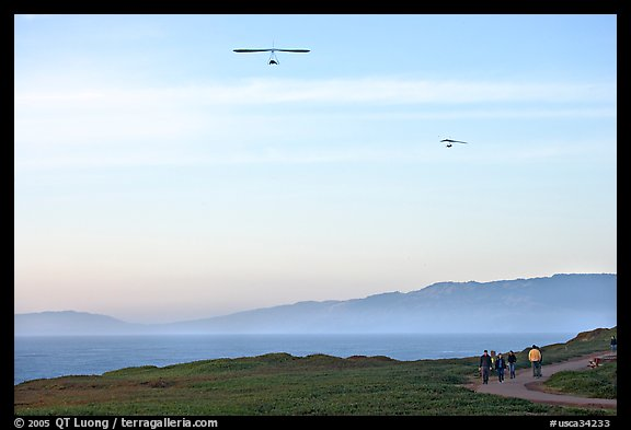 Hang gliders soaring above hikers, Fort Funston, late afternoon. San Francisco, California, USA